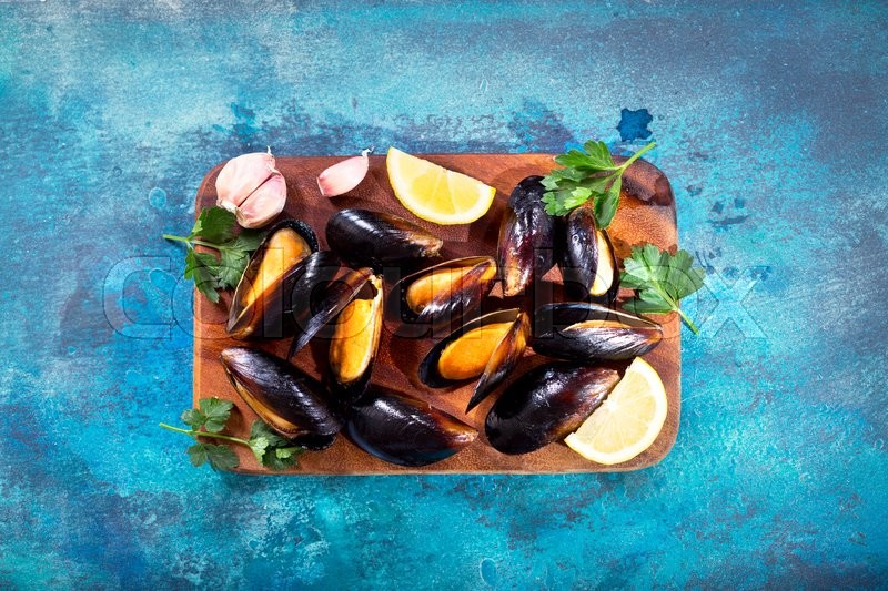Stock image of ' mussels with parsley and lemon on wooden board, top view'