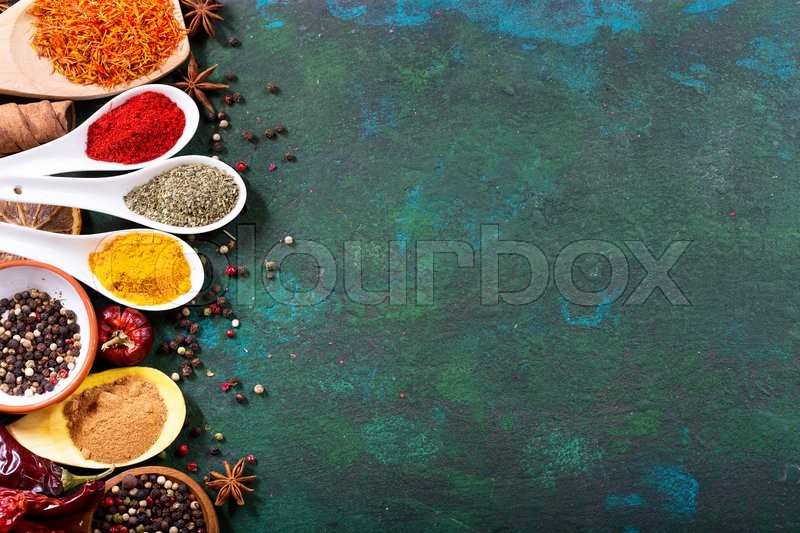 Stock image of 'various spices in spoons on old green background, top view'