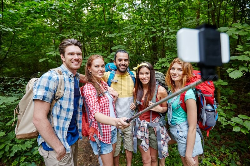 Stock image of 'technology, travel, tourism, hike and people concept - group of smiling friends walking with backpacks taking picture by smartphone on selfie stick in woods'