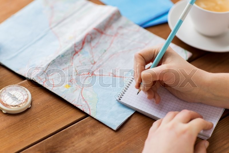 Vacation, tourism, travel, destination and people concept - close up of traveler hands with blank notepad and pencil, stock photo