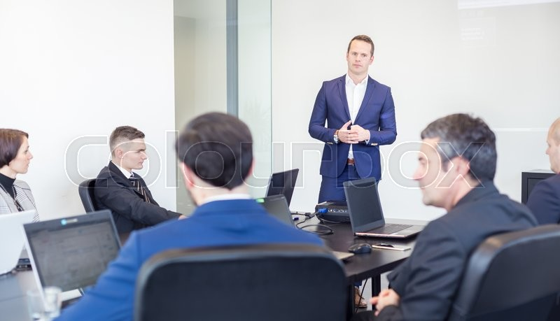 Stock image of 'Successful team leader and business owner  leading informal in-house business meeting. Businessman working on laptop in foreground. Business and entrepreneurship concept.'