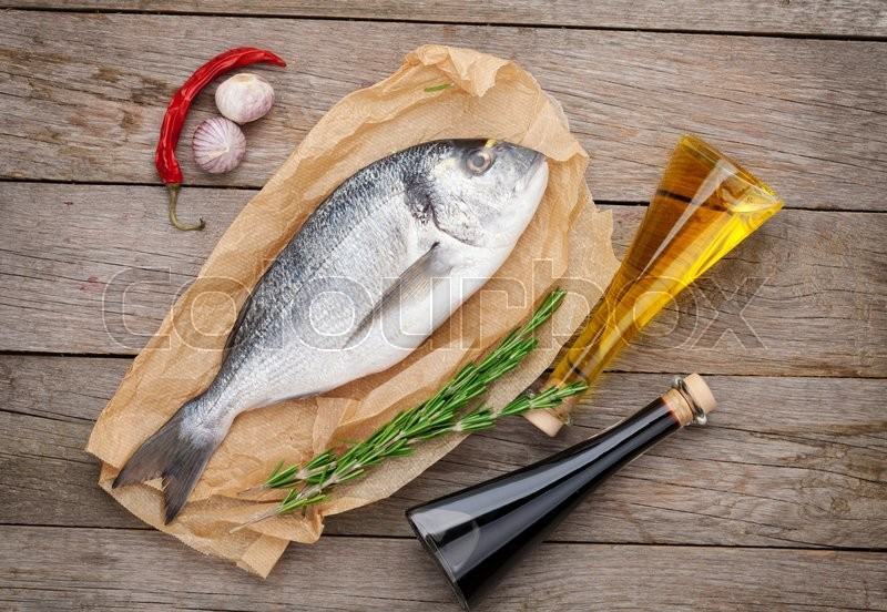 Stock image of 'Fresh dorado fish cooking with spices and condiments on wooden table'