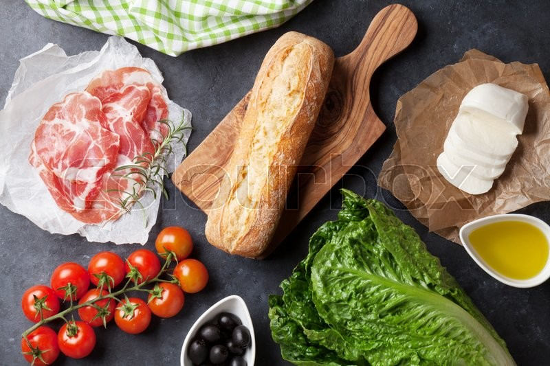 Stock image of 'Ciabatta sandwich cooking with romaine salad, prosciutto and mozzarella cheese over stone background. Top view'