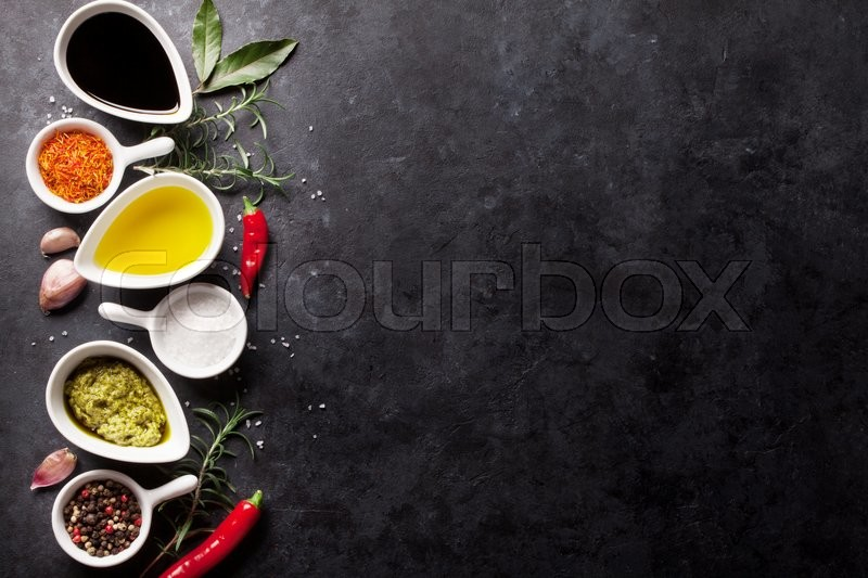 Herbs, condiments and spices on stone background. Top view with copy space, stock photo