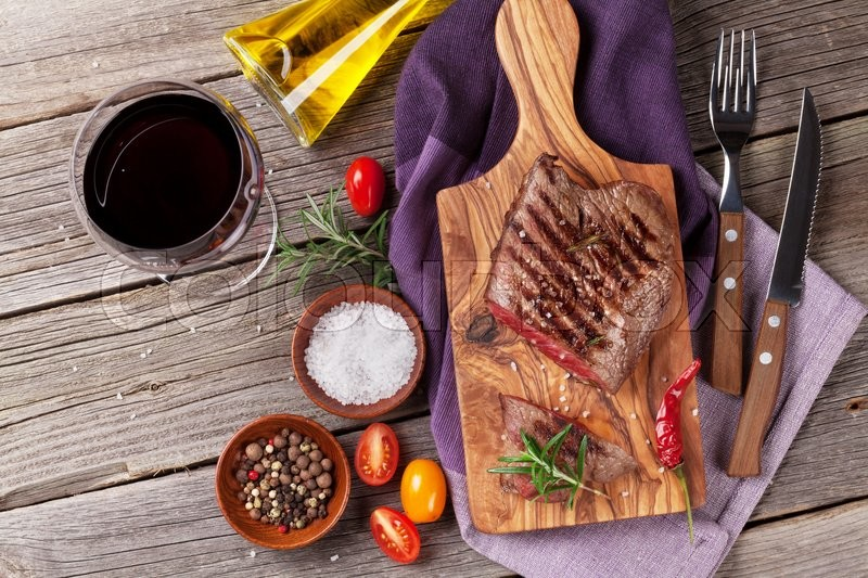 Grilled beef steak with rosemary, salt and pepper and red wine on wooden table. Top view, stock photo
