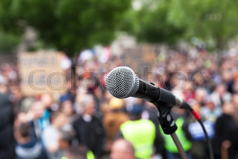 Microphone in focus against blurred crowd. Political rally, stock photo