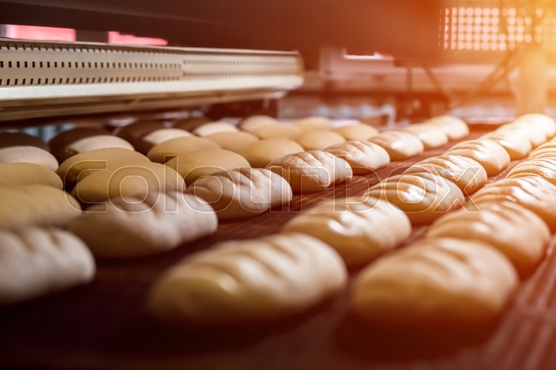 Dessert bread baking in oven. Production oven at the bakery. Baking bread. Manufacture of bread, stock photo