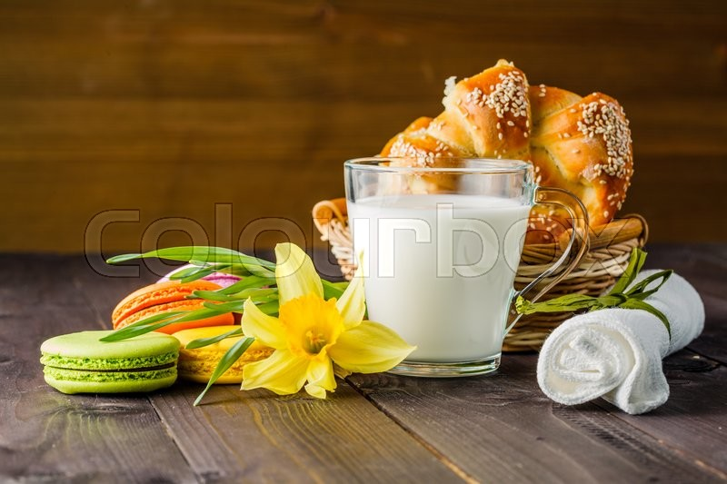 Stock image of 'Milk with pastry and spring yellow flower on table'