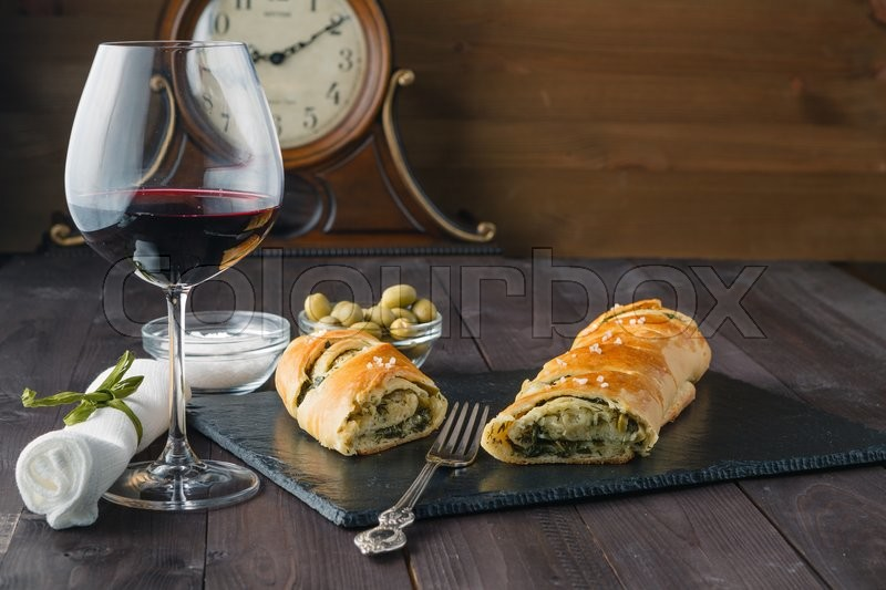 Stock image of 'French stuffed bread with olives and glass of red wine on table'