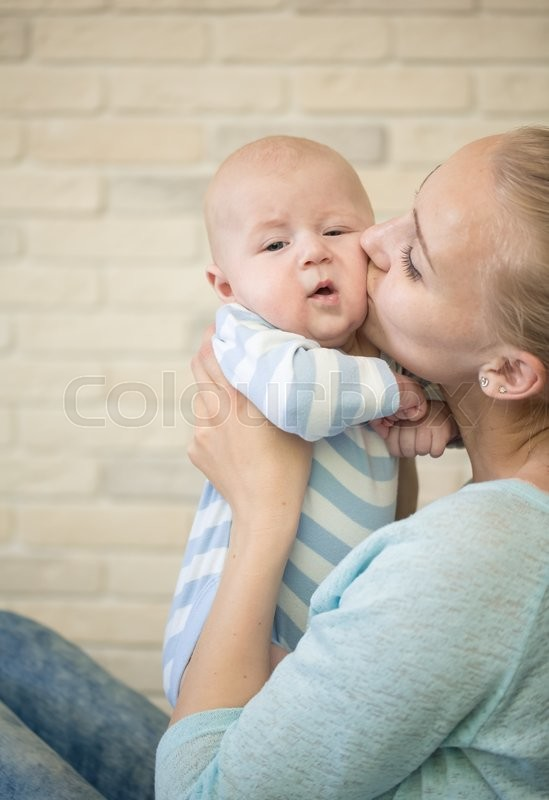 Stock image of 'Portrait of happy young mother and baby at home'