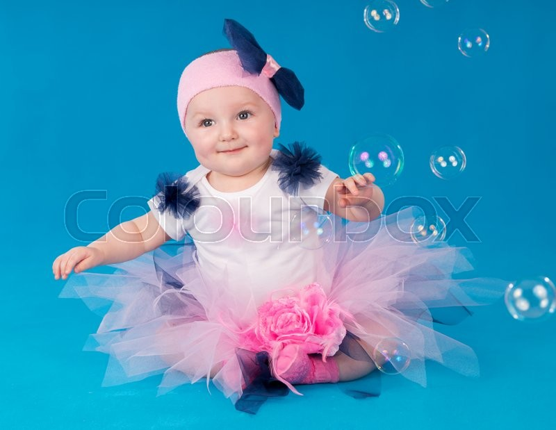 Stock image of 'Happy small girl sitting on the floor on a blue background'
