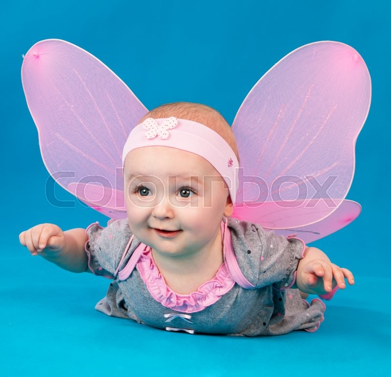 Stock image of 'Happy small girl butterfly wings sitting on the floor on a blue background'