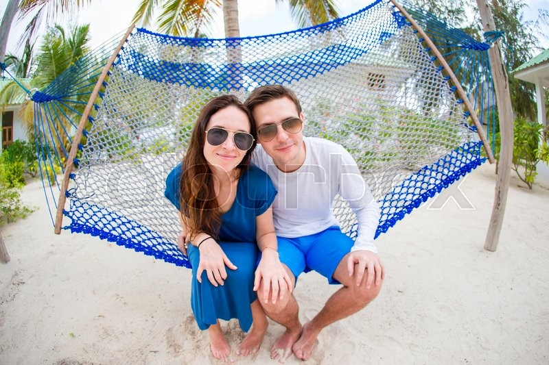 Happy couple on tropical vacation relaxing in hammock, stock photo