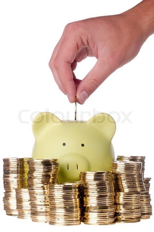 human hand putting a golden coin into a green piggy bank