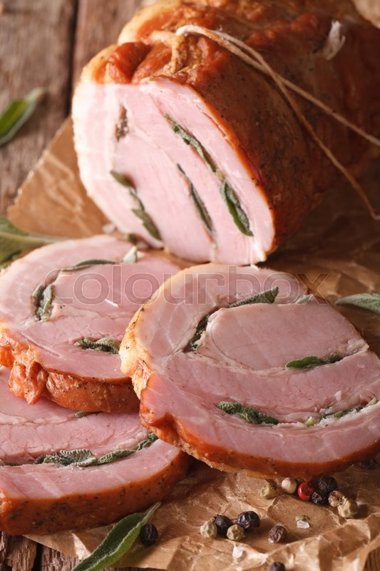 Stock image of 'Spicy baked pork stuffed with sage close up on the table. vertical, rustic\'
