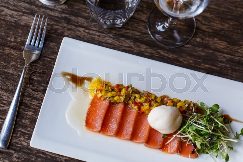 Stock image of 'Carpaccio of salmon on a white plate in restaurant'
