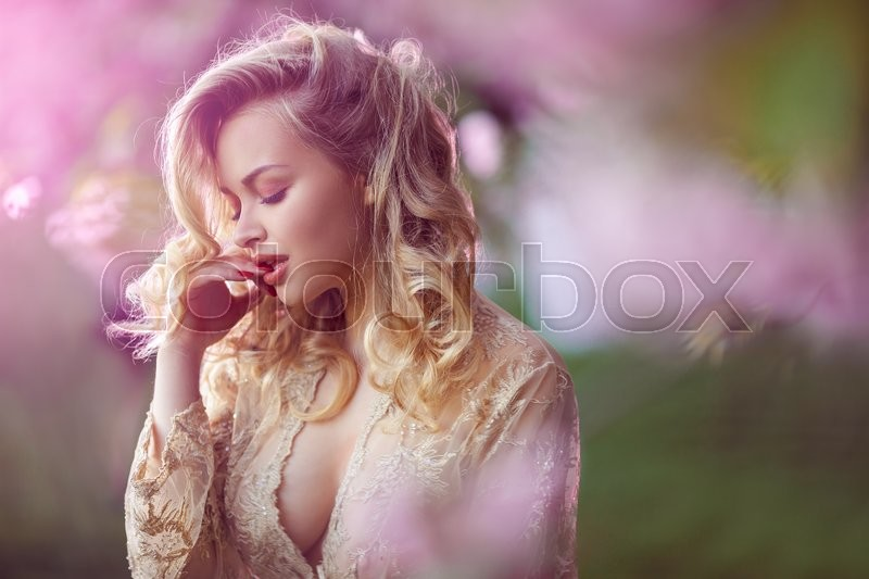 Sensual young woman standing in sexy transparent dress at blossoming pink sakura tree in the garden. Beauty of woman and nature.Portrait of beautiful model with curly blonde hair. Closed eyes in passion, stock photo