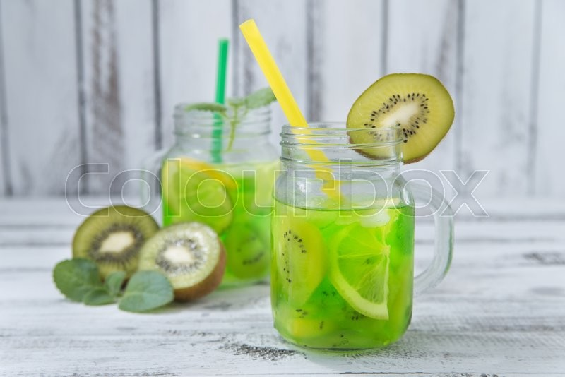 Stock image of 'homemade lemonade with  kiwi, lemon, mint in glass on a wooden rustic table'