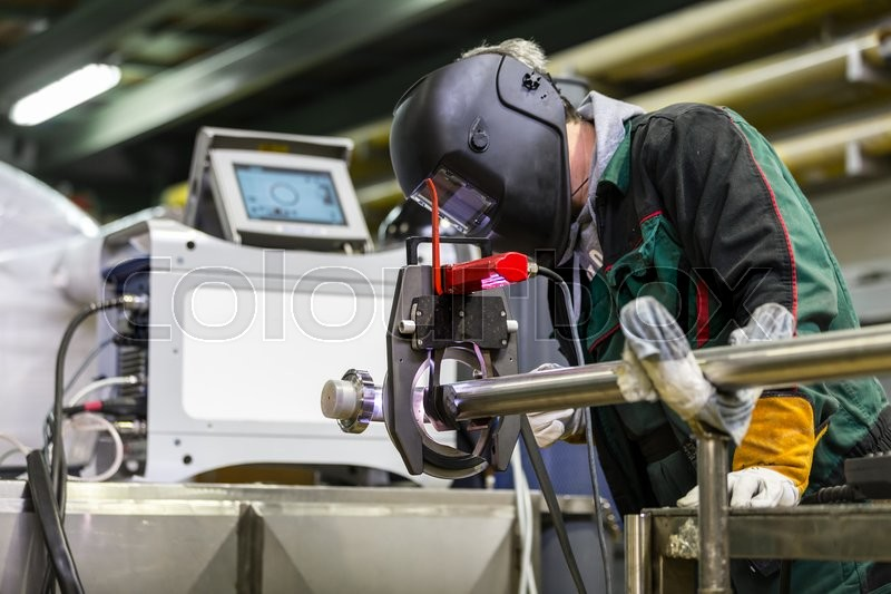 Stock image of 'Industrial operator setting  computer controlled process of orbital welding machine in inox pipes manufacturing workshop.'