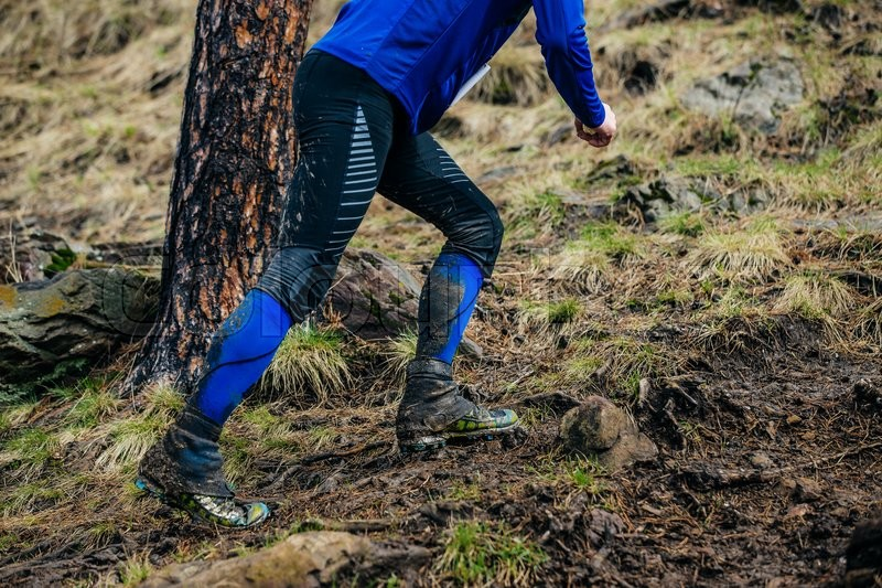 Stock image of 'legs male athlete running uphill in mud during a Mountain marathon'