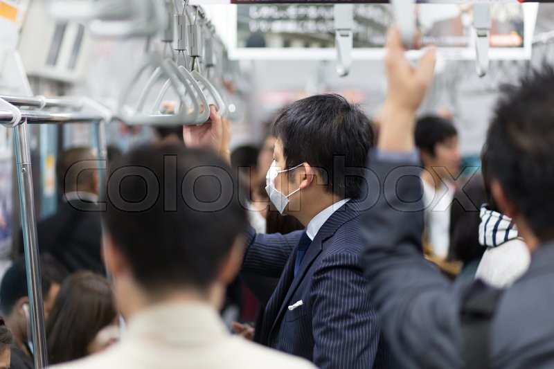 Stock image of 'Passengers traveling by Tokyo metro. Business people commuting to work by public transport in rush hour. Shallow depth of field photo. Horizontal composition.'