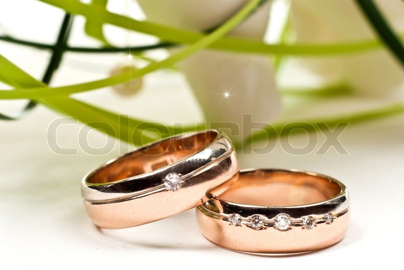 Pair of golden wedding rings with rose bouquet Macro photo Stock