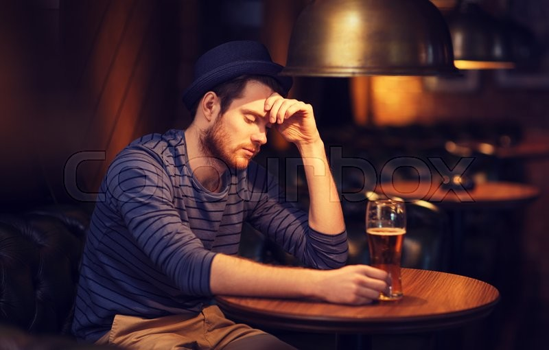 Stock image of 'people, loneliness, alcohol and lifestyle concept - unhappy single young man in hat drinking beer at bar or pub'
