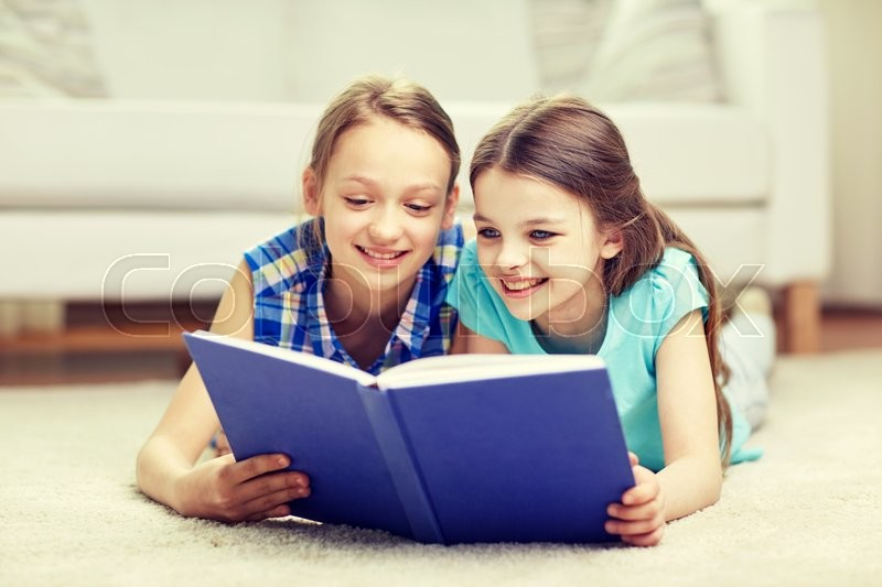 Stock image of 'people, children, friends, literature and friendship concept - two happy girls lying on floor and reading book at home'