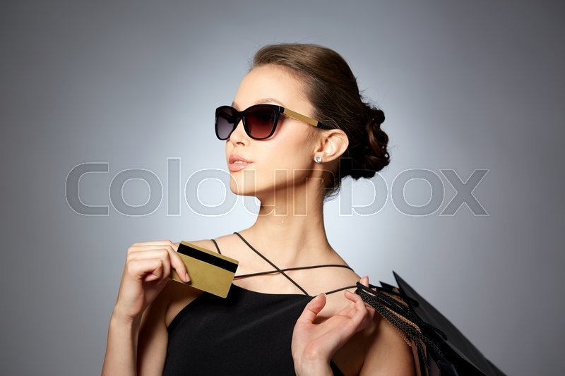 Sale, finances, fashion, people and luxury concept - happy beautiful young woman in black sunglasses with credit card and shopping bags over gray background, stock photo
