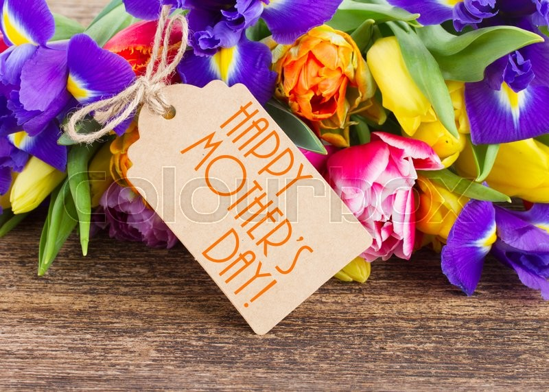 Stock image of 'spring tulips and  irises with  happy mothers day  paper tag on wooden background'