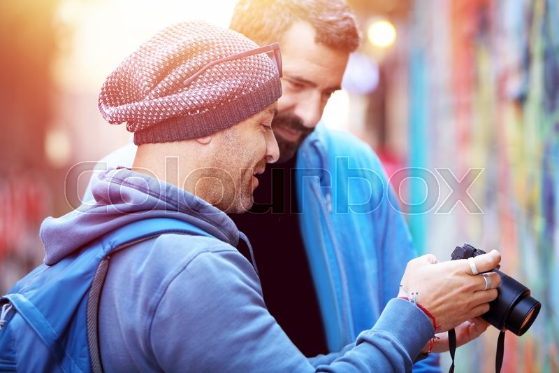 Stock image of 'Two happy friends outdoors, conversing and looking at the images on the photo camera, best friends enjoying active summer vacation '