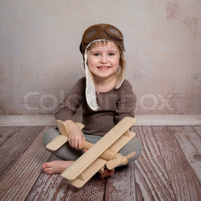 Stock image of 'smiling little girl with wooden plane in hands sitting on the floor'