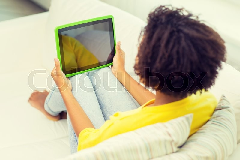 Stock image of 'people, technology, advertisement and leisure concept - happy african american young woman sitting on sofa with tablet pc computer black blank screen at home'