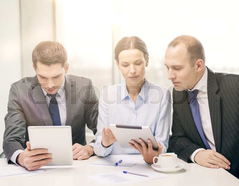 Stock image of 'business, technology and office concept - serious business team with tablet pc computer, documents and coffee having discussion in office'