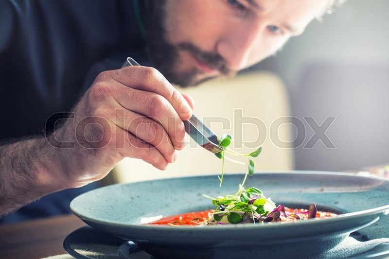 Chef in hotel or restaurant kitchen cooking, only hands. He is working on the micro herb decoration. Preparing tomato soup, stock photo
