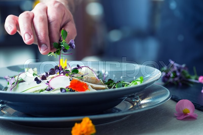 Chef in hotel or restaurant kitchen cooking, only hands. He is working on the micro herb decoration. Preparing vegetable salad with pieces of grilled chicken meat - virgin sirloin, stock photo