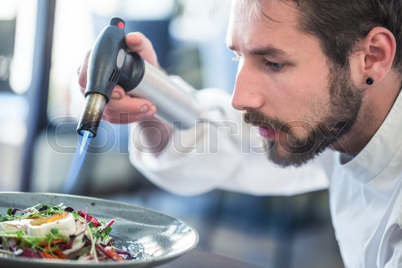 Chef preparing food. Cook flamed using Flambé gun pistol. Chef flambe vegetable salad with goat cheese. Gourmet cuisine, stock photo