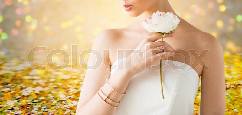 Stock image of 'glamour, beauty, jewelry and luxury concept - close up of beautiful woman with golden ring and bracelet holding flower over golden holidays lights background'