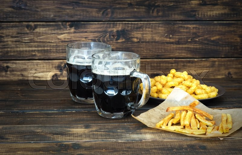 Stock image of 'Two mugs of dark beer with fries and peanut puffs on wooden background'
