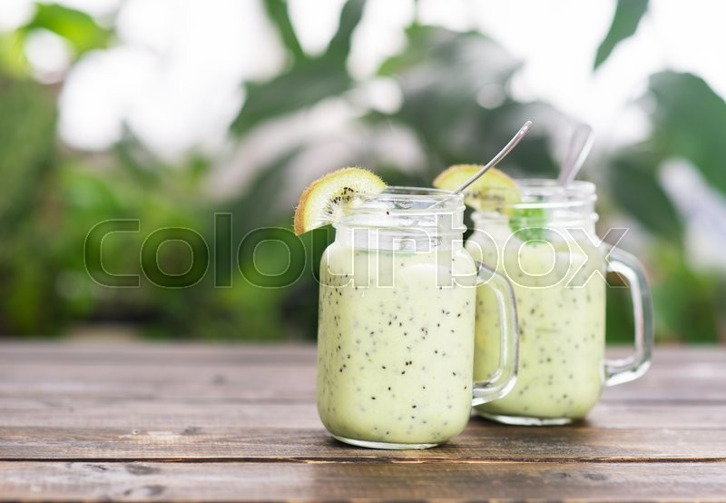 Stock image of 'Kiwi green detox smoothie in two cups'