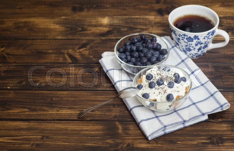 Stock image of 'Fitness wheat muesli with yogurt, blackberry and tea on dark wooden table '