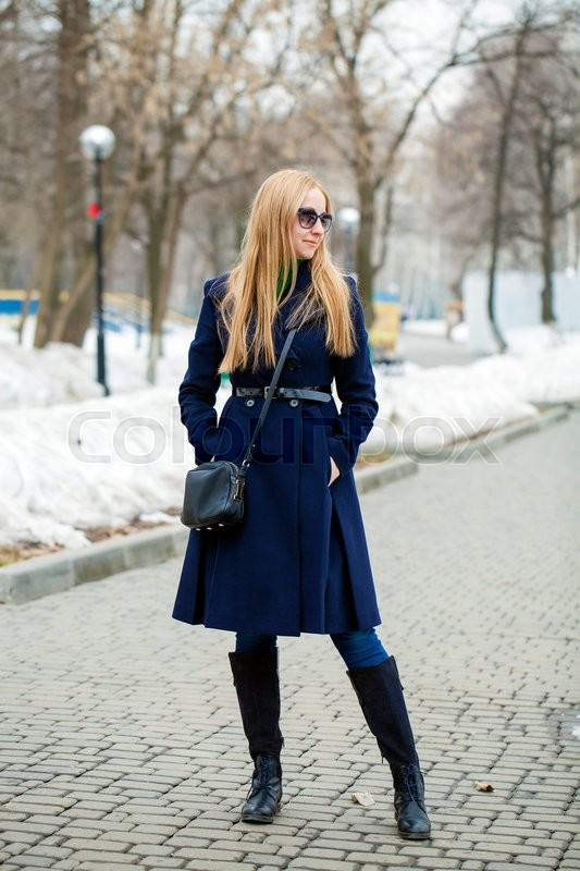 Stock image of 'Young blonde woman in a blue coat posing on a background of a winter park'