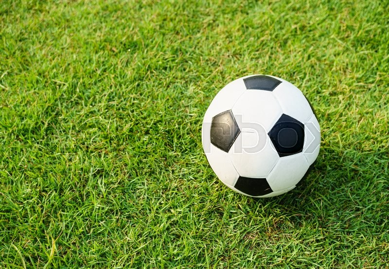 Stock image of 'A football (soccer) on green grass field background'
