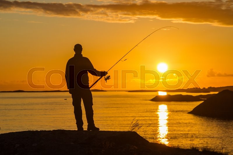 Stock image of 'Silhouette of a fisherman holding a spinning rod in front of a sunset.'