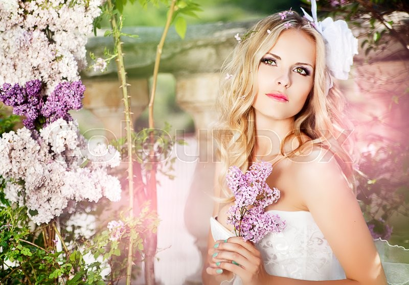 Stock image of 'portrait of young beautiful woman girl on background of bougainvillea purple violet flowers in blossom'