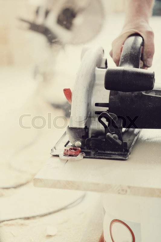 Stock image of 'Man with electric saw at work'