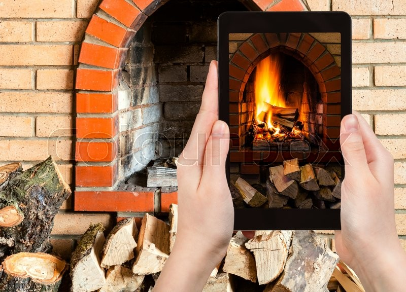 Stock image of 'comfortable holiday concept - tourist photographs fire in fireplace on tablet pc'