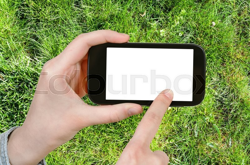 Stock image of 'gardening concept - farmer photographs green grass of lawn on smartphone with cut out screen with blank place for advertising'