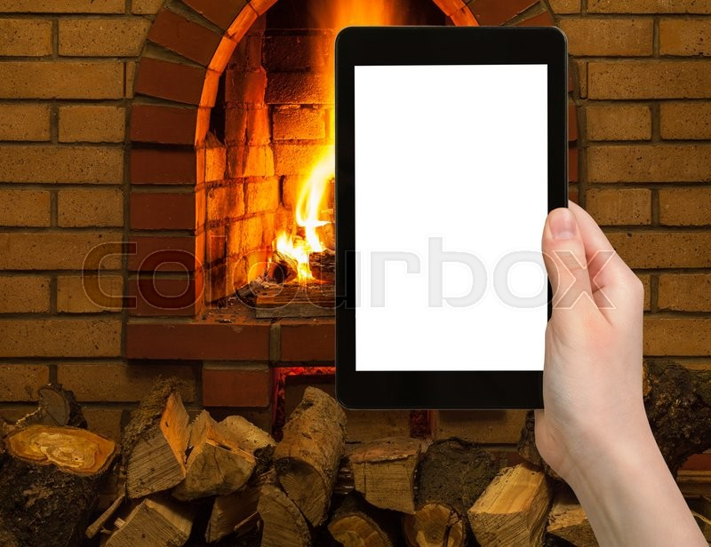 Stock image of 'comfortable holiday concept - tourist photographs fireplace on tablet pc with cut out screen with blank place for advertising'