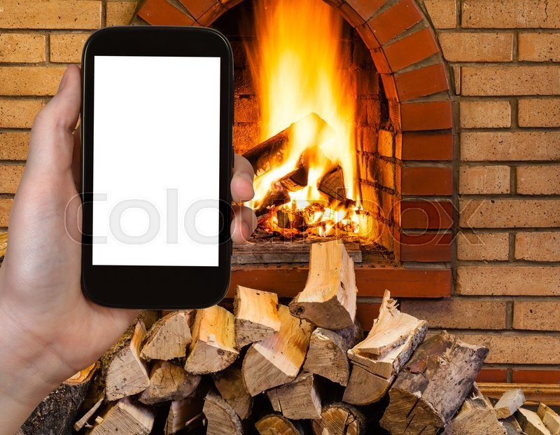 Stock image of 'comfortable holiday concept - tourist photographs fireplace on smartphone with cut out screen with blank place for advertising'